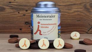 Innenelemente Hörnke präsentiert sich mit Logo auf weißer belgischer Schokolade